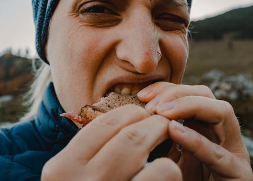 Wurstbrot essen wandern brotzeit wurstbrot beissen unterwegs essen und trinken hunger hände blick abbeißen natur landschaft sport ernährung nahrung energie