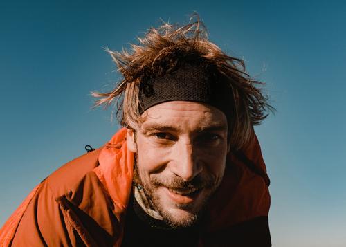 Portrait von jungem Wanderer brecherspitze spitzing wandern mann Natur gipfel portrait sportlich gesicht bart stirnband haare warm sonne blauer himmel