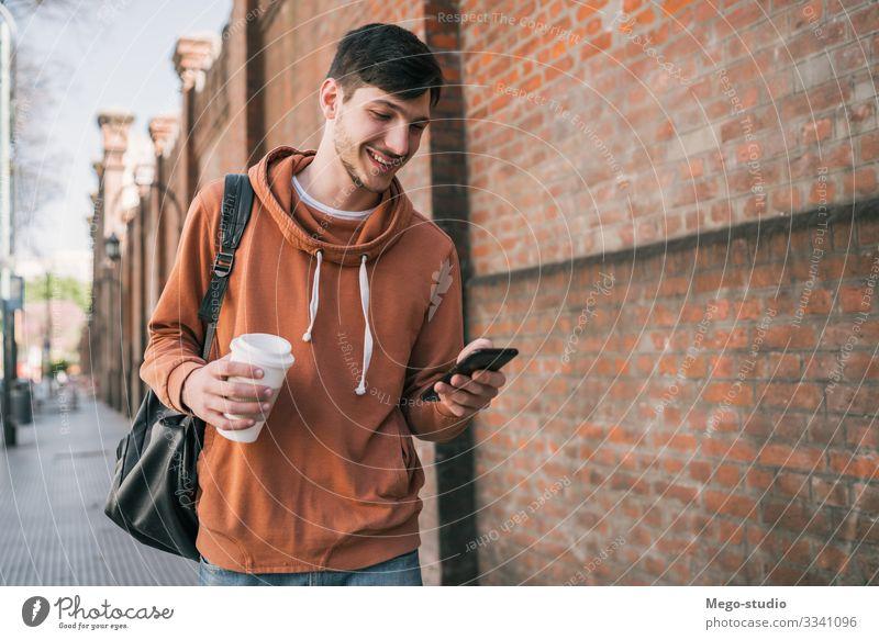 Ein Mann, der sein Handy benutzt. Lifestyle Stil Freude Glück Zufriedenheit Telefon PDA Technik & Technologie Mensch Erwachsene 1 18-30 Jahre Jugendliche Straße