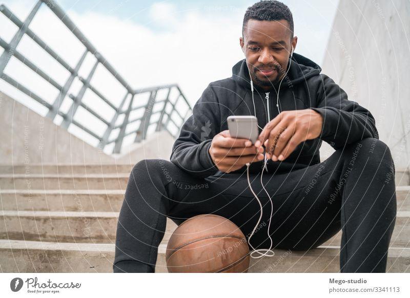 Sportler, der sein Mobiltelefon benutzt. Lifestyle Freizeit & Hobby Telefon PDA Technik & Technologie Mensch Mann Erwachsene 1 30-45 Jahre Fitness genießen