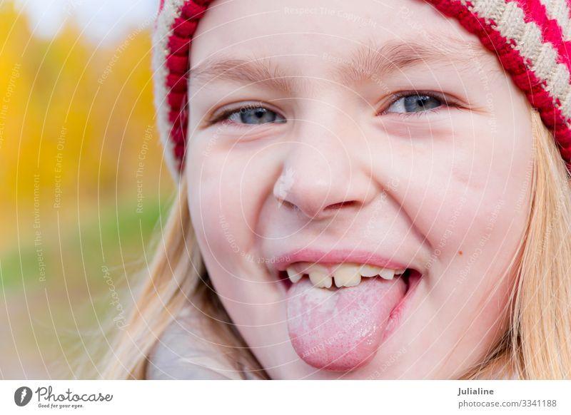 Süßes Mädchen streckt die Zunge heraus Kind Schulkind Frau Erwachsene Kindheit Herbst blond Lächeln lang niedlich blau weiß Gefühle ausmachen Vorschulkind eine