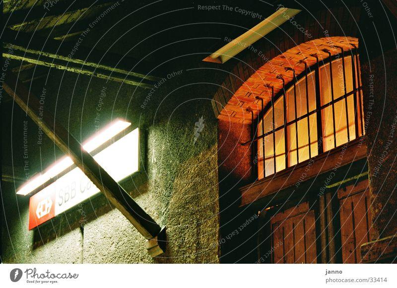 Lichtspiel im Hinterhof Nacht Bahnanlage Architektur Güterschuppen Froschperspektive Detailaufnahme Bahnhof Schweiz Gitter Doppeltür Backstein Außenbeleuchtung