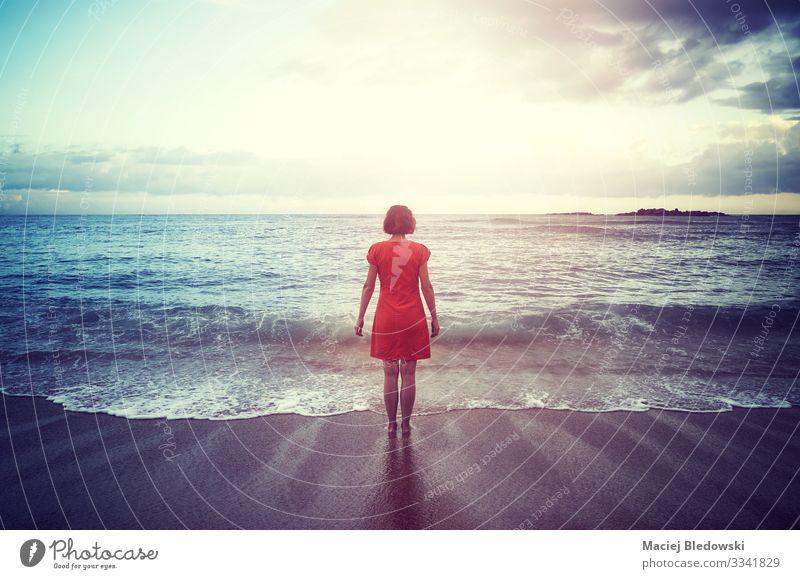 Frau, die bei Sonnenuntergang an einem Strand mit Blick auf den Horizont steht, Lifestyle Erholung Freizeit & Hobby Ferien & Urlaub & Reisen Freiheit Sommer
