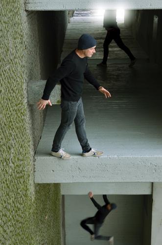 stay here Mensch maskulin Mann Erwachsene 1 45-60 Jahre Stadt Haus Fassade grau gehen Doppelgänger Le Parkour Illusion gedreht verdreht Klettern hängen Beton