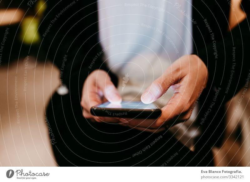 Nahaufnahme einer jungen Frau, die in einem Café oder Restaurant in einem Innenraum ein Mobiltelefon benutzt. Unkenntnis der Lebensweise von Personen Handy