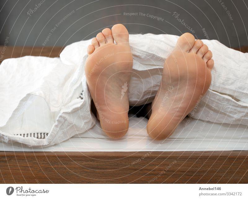 Ein Paar Füße allein im Bett auf weißen Blättern Haut Erholung Kind Schule Mensch Junge Mann Erwachsene Fuß schlafen bequem Farbe eine Decke Barfuß lügen