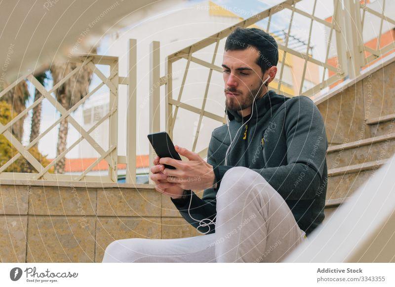 Nachdenklicher Läufer nutzt Telefon und macht Pause Mann Browsen benutzend besinnlich ernst Training Erholung Treppe aktiv männlich Smartphone nachdenklich