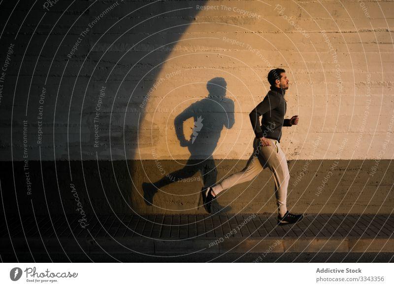 Junger Mann joggt auf der Straße in der Stadt joggen Sport Training Gesundheit aktiv Fitness urban männlich Beine Läufer Athlet Lifestyle Sportbekleidung Übung
