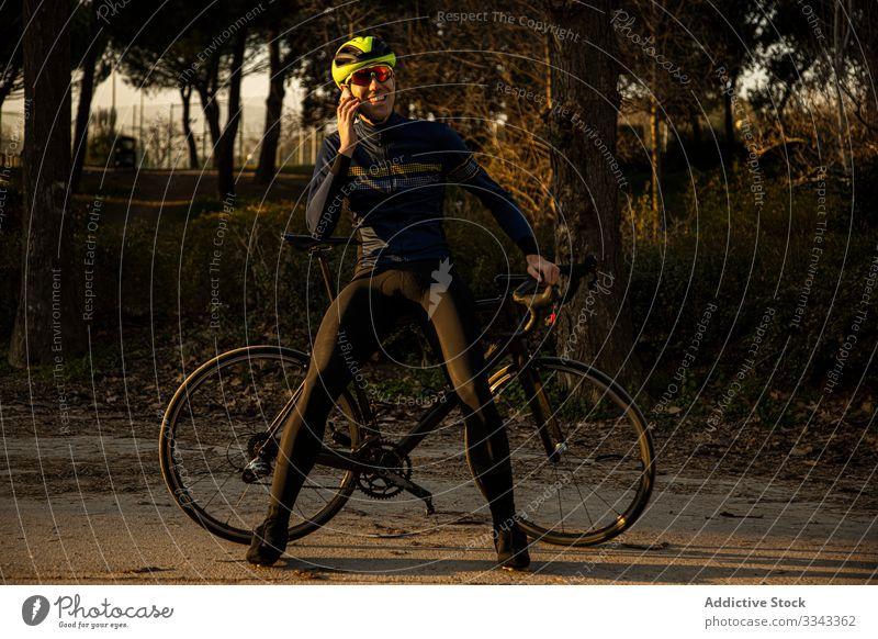 Mann fährt mit dem Handy in einem Park Rad Freiheit Schutzhelm Mitfahrgelegenheit Fahrrad Radfahrer Übung Fitness Person Sport Abenteuer Gesundheit Lifestyle