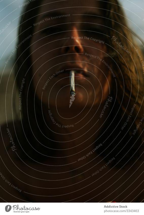 Frau schaut in die Kamera, während sie eine Zigarette raucht Rauchen jung Dame lockig blau Himmel auflehnen Hipster Teenager Lächeln genießen Tabak Sucht Sommer