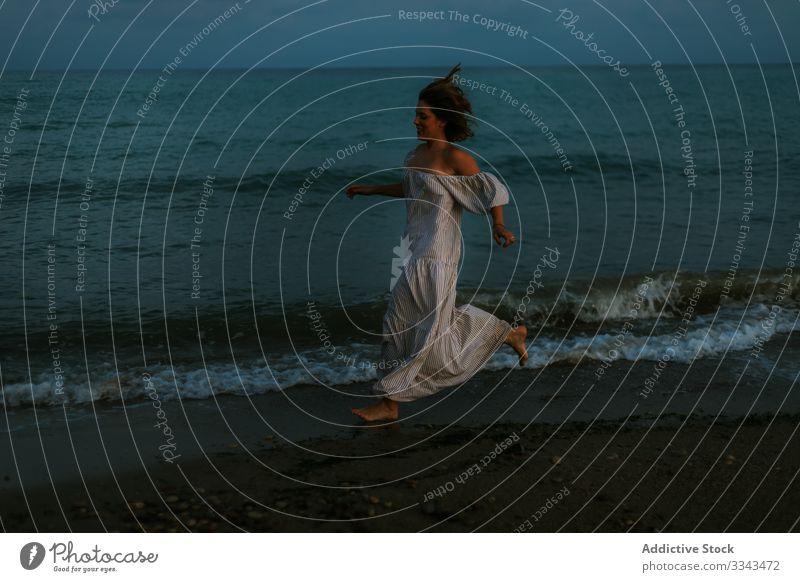 Weibliche Touristen am Meer Frau Strand Wellen Seeküste Barfuß Meeresufer Himmel Himmel (Jenseits) Abenddämmerung Wolken Dame laufen Küstenlinie leer einsam