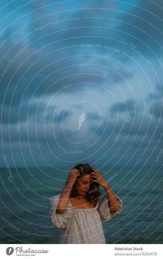 Weibliche Touristen am Meer Frau Strand Wellen Seeküste Meeresufer Himmel Himmel (Jenseits) Abenddämmerung Wolken Dame laufen Küstenlinie leer einsam blau Kleid