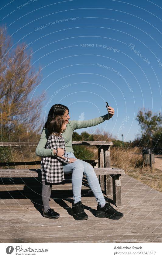 Glückliche ethnische Mutter, die mit ihrem Kind Selbsthilfe nimmt Selfie Mädchen Telefon benutzend Foto Lächeln Umarmung Zusammensein sich[Akk] entspannen Natur
