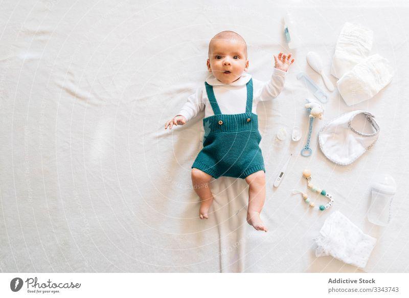 Überraschtes Baby im Bett liegend Lügen Spielzeug neugeboren heimwärts überrascht neugierig Säugling offener Mund bezaubernd Kind klein niedlich wow süß Pyjama