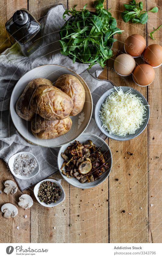 Schmackhaftes Gericht aus Kartoffeln und frischen Zutaten auf dem Tisch gefüllt Bestandteil rustikal hölzern Speise selbstgemacht grün Kraut Gewürz gebraten