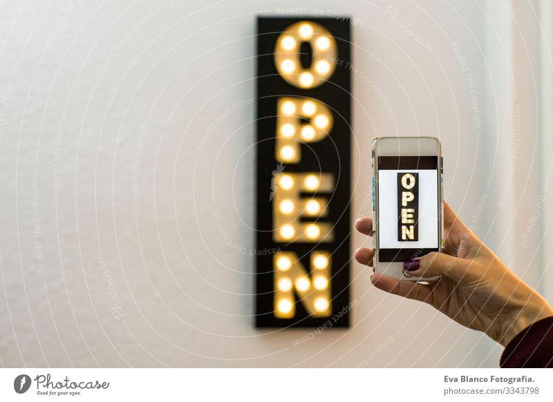 Frau, die ein Foto mit dem Handy zu einer Open Sign Neon Light Shop Business Dekoration macht. Glühbirnen. Weißer Hintergrund. Horizontale Ansicht Lifestyle