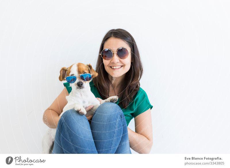 Hübsche junge Frau, die zu Hause mit ihrem kleinen süßen Hund spielt. Porträt des Lebensstils. Konzept der Liebe zu Tieren. weißer Hintergrund. Beide tragen eine Sonnenbrille