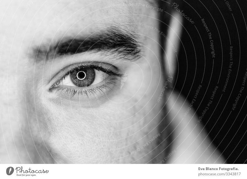 Nahaufnahme eines jungen Mannes in der Mitte der Seite. Atelieraufnahme. Led-Ringreflexion in den Augen Kopf weiß Mensch schwarz dramatisch Lifestyle 1
