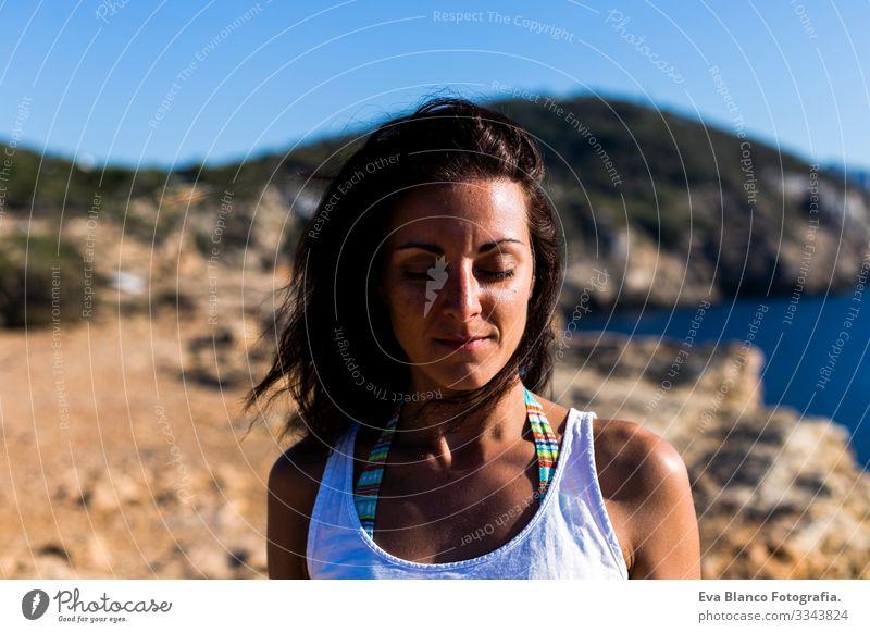 Porträt einer jungen schönen Frau, die entspannt mit geschlossenen Augen am Strand bei Sonnenuntergang steht. Der Wind bewegt ihr Haar. Urlaubs- und Entspannungskonzept
