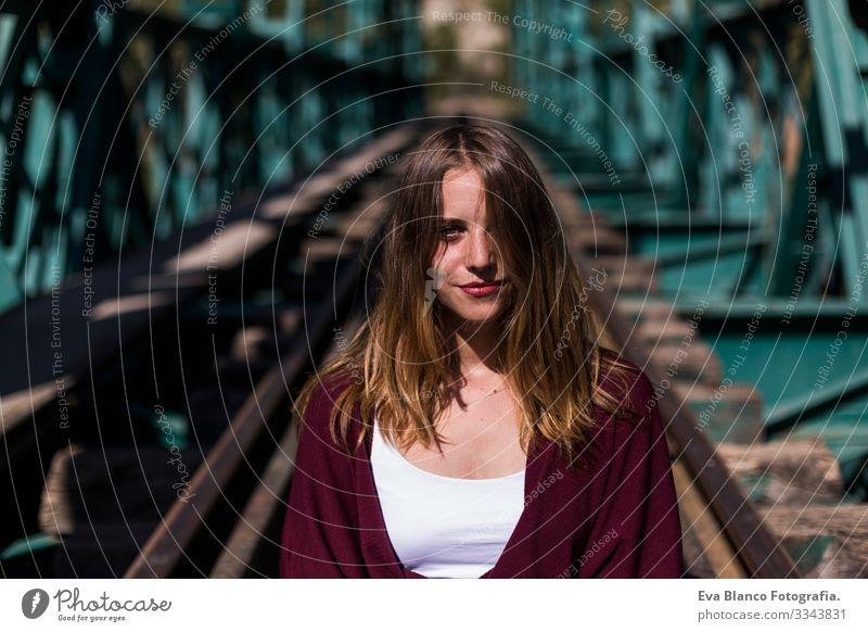 Porträt einer jungen schönen Frau, die in der Eisenbahn sitzt und in die Kamera schaut. Die Haare bedecken die Hälfte ihres Gesichts. Im Freien. Sonnig hübsch
