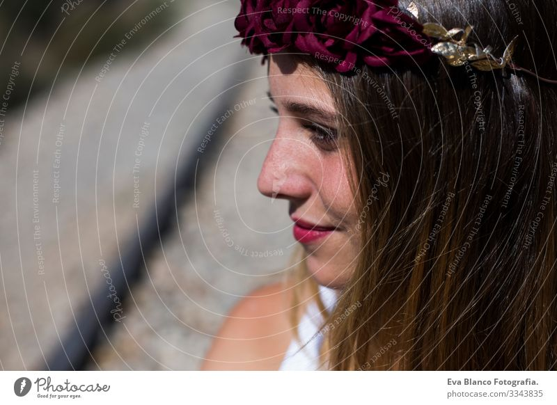 Profil Gesicht Portrait Schöne junge Frau mit einem roten Rosenkranz auf dem Kopf. Rote Lippen. Im Freien. Sonnig. Die Eisenbahn. Lebensstil Freiheit