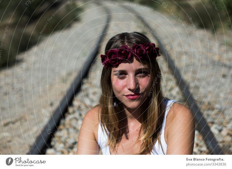 Porträt einer jungen, schönen Frau, die einen roten Rosenkranz auf dem Kopf trägt und in die Kamera schaut, sitzend auf einer Eisenbahn. Im Freien. Sonnig. Lebensstil