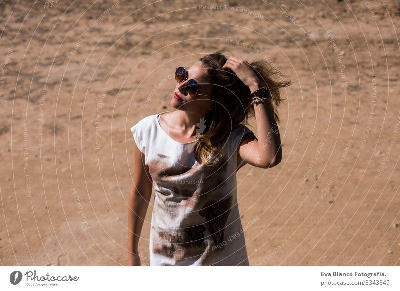 junge schöne Frau, die mit den Haaren spielt. im Freien. sonnig. Freiheit Beautyfotografie Kaukasier Blume Außenaufnahme Jugendliche Erotik Glück Gesicht