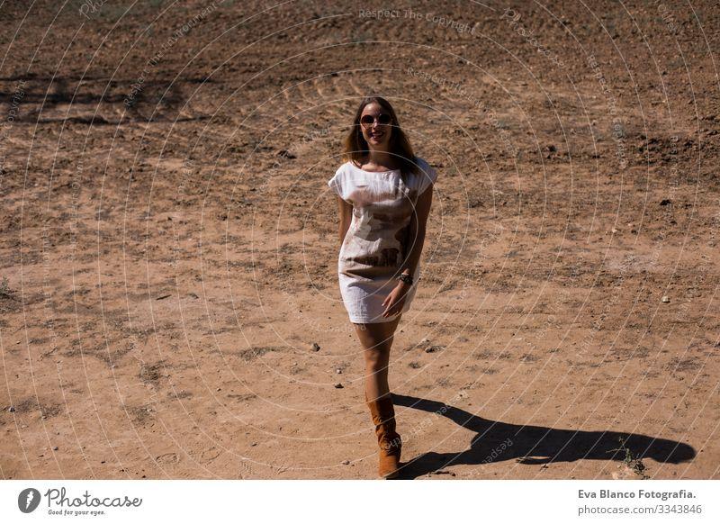 schöne junge Frau, die geht und lächelt. Lässige Kleidung. Lebensstil Beautyfotografie Kaukasier Blume Außenaufnahme Jugendliche Erotik Glück Gesicht Lächeln