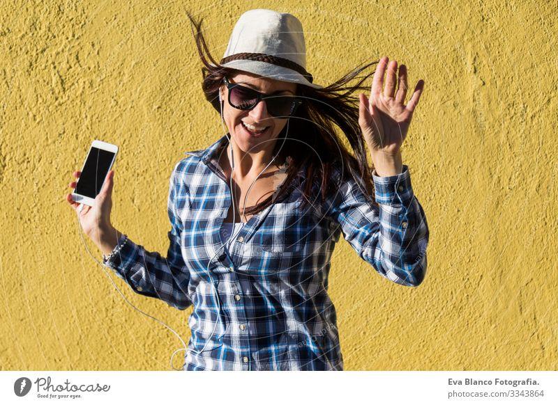 eine glückliche, schöne junge Frau, die Musik hört und sich über dem gelben Hintergrund amüsiert. Sie trägt einen Hut und eine moderne Sonnenbrille. Porträt