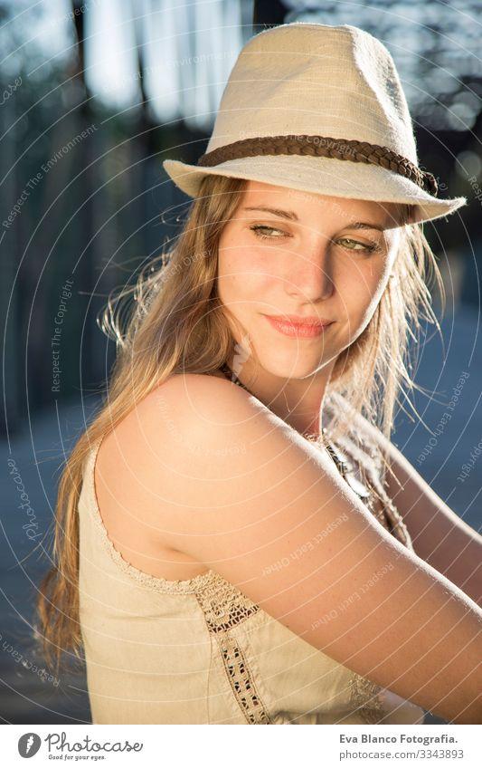 Porträt einer jungen Frau bei Sonnenuntergang Jugendliche Außenaufnahme Glück blond Hut blaue Augen Brücke Sommer Sonnenstrahlen Behaarung Fröhlichkeit