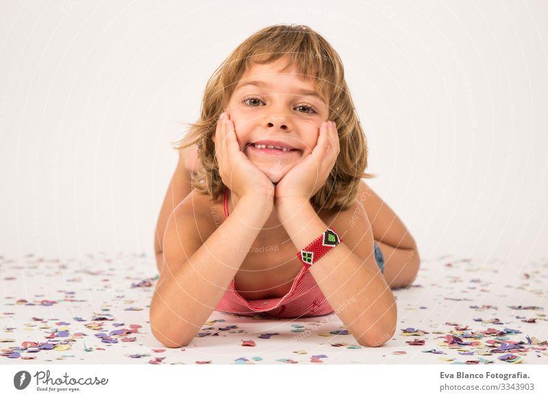 Porträt eines kleinen Mädchens. drinnen, Konfetti auf dem Boden. weißer Hintergrund Freude Kind niedlich Lifestyle-Glück heiter schön Behaarung Innenaufnahme