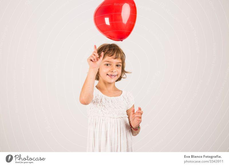 Kind, das im Studio mit einem roten Ballon spielt. Spaß, Lebensstil. weißer Hintergrund Porträt Freude niedlich Lifestyle-Glück heiter schön klein Behaarung