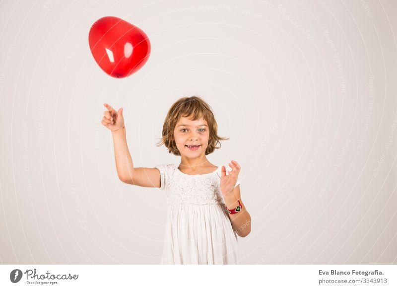 Kind, das im Studio mit einem roten Ballon spielt. Spaß, Lebensstil, weißer Hintergrund Porträt Freude niedlich Lifestyle-Glück heiter schön klein Behaarung