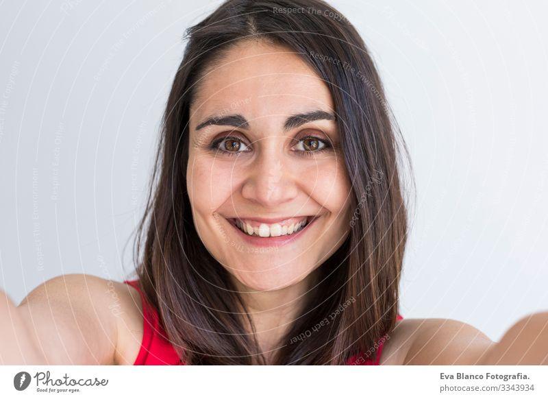 Eine glückliche schöne Frau, die einen Selfie mit einem Smartphone auf weißem Hintergrund nimmt. Lebensstil. Das Tragen von Freizeitkleidung. Jugendliche