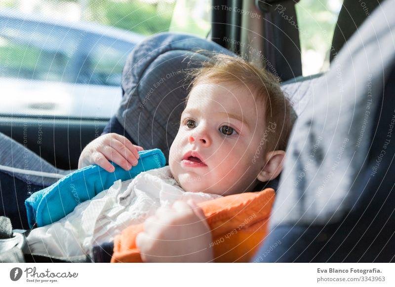 Ein süßes blondes Mädchen, das im Autositz angeschnallt ist und sich glücklich auf den Weg der Straße macht. Frühjahr oder Sommersaison Gürtel klein Kind
