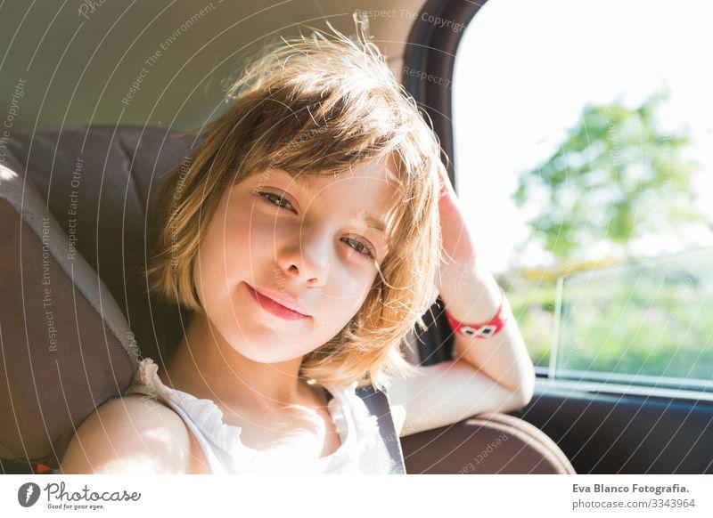 süßes Kleinkind, blondes Mädchen, im Autositz angeschnallt, glücklich wird sich auf den Weg der Straße machen, Sonnenblendung reflektiert Gürtel Sommer klein