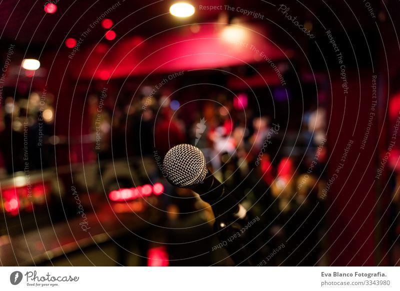 Mikrophon auf einer Komödien-Ständerbühne mit farbenfrohem Bokeh , kontrastreichem Bild. Mikrofon Party Nacht Club Mensch Menge Weihnachten & Advent rot