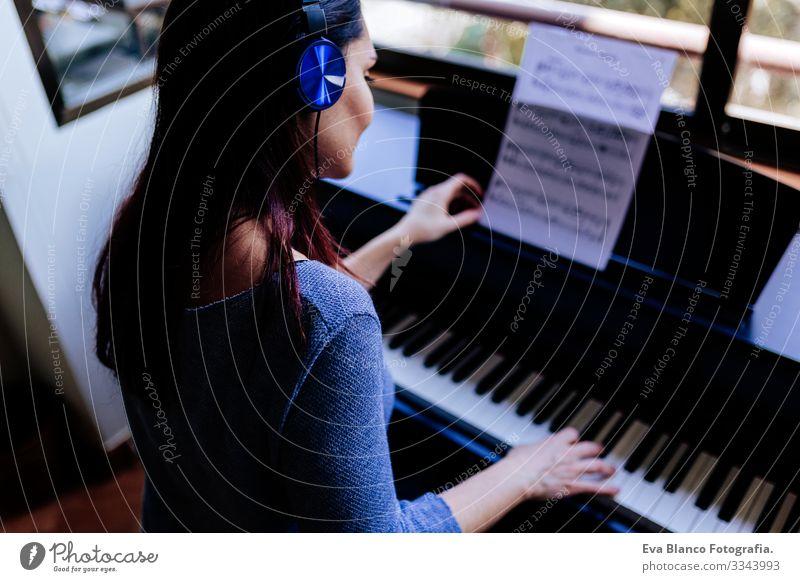 junge Frau, die beim Klavierspielen ein Notenblatt in der Hand hält. Musikkonzept im Innenbereich. Rückansicht Stil Mensch Schlüssel Hinweis Schulunterricht