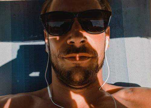 Chillen und Musikhören im Urlaub musikhören kopfhörer liegen urlaub bart mann junger mann sonnebrille sommer sommerurlaub sonnenliege portrait ferien erholung