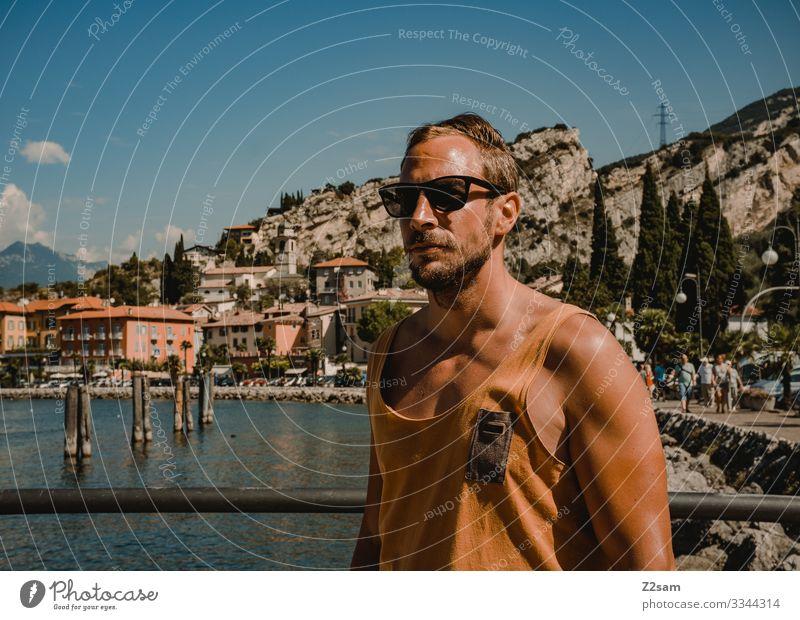 Junger Mann im Urlaub | Torbole Gardasee gardasee mann strand torbole seeufer berge Berge u. Gebirge Außenaufnahme Wasser Italien Natur Landschaft Sommer hafen