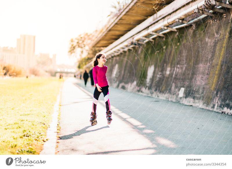 Kleine Schlittschuhläuferin, die an einem sonnigen Tag auf einem Park Schlittschuh läuft Lifestyle Freude Glück schön Gesundheit sportlich Leben