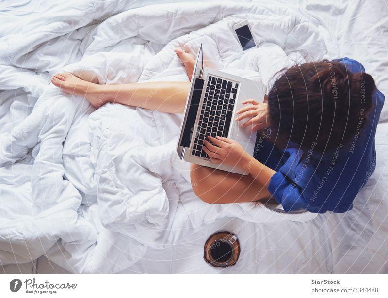 Junge Frau, die zu Hause in ihrem Bett Kaffee trinkt, Ansicht von oben schön Leben Erholung lesen Schlafzimmer Arbeit & Erwerbstätigkeit Arbeitsplatz Computer