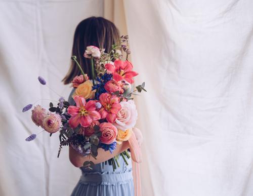 Junge Frau in einem hellblauen Kleid mit einem Blumenstrauß in der Hand. Lifestyle elegant Stil Glück schön Hochzeit Erwachsene brünett modern niedlich retro