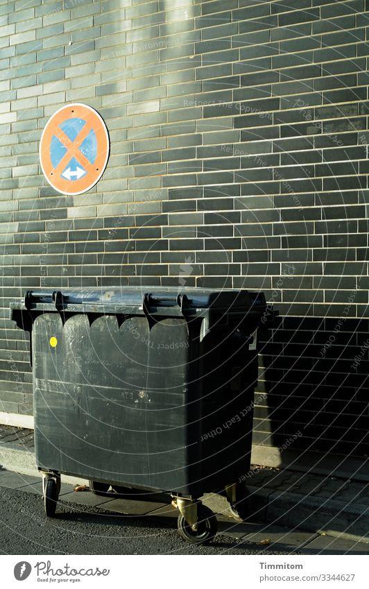 Müllbehälter Stadt Mauer Wand Straße Kunststoff Schilder & Markierungen Verkehrszeichen warten blau grau rot schwarz Asphalt Schatten Backstein Farbfoto