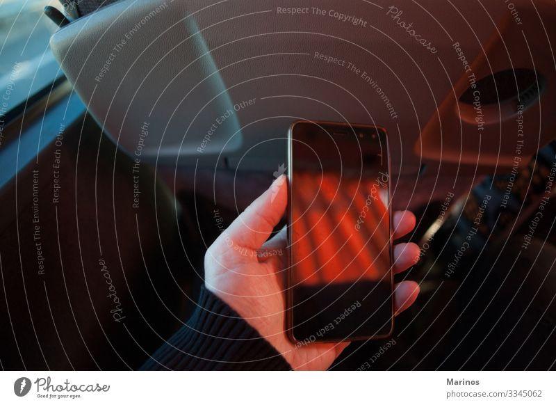 Ein Mann mit einem Mobiltelefon in einem Bus. Ausflug Telefon Technik & Technologie Erwachsene Hand Verkehr Kommunizieren Innenaufnahme