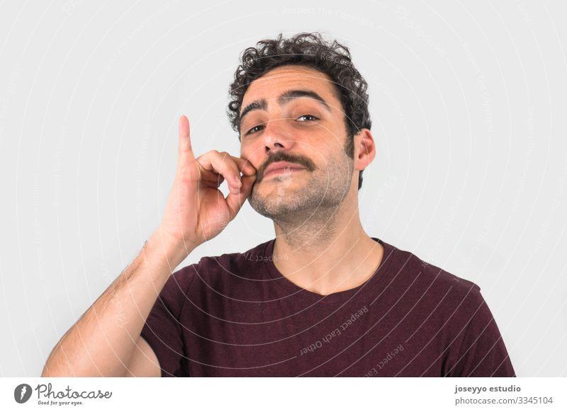 Brauner, lächelnder, gut aussehender Mann, der seinen Schnurrbart mit einem lila T-Shirt berührt. Lustiges Porträt. Grauer Hintergrund. 30-40 Jahre Erwachsener