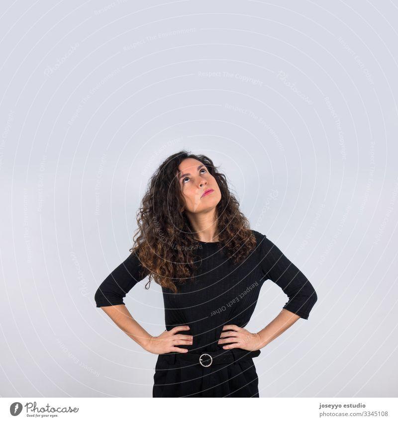 Lockenhaarige, brünette Frau in Schwarz, die mit nachdenklicher Geste ihre Hände auf die Taille legt und nach oben schaut. 30-40 Jahre Inserat Einstellung
