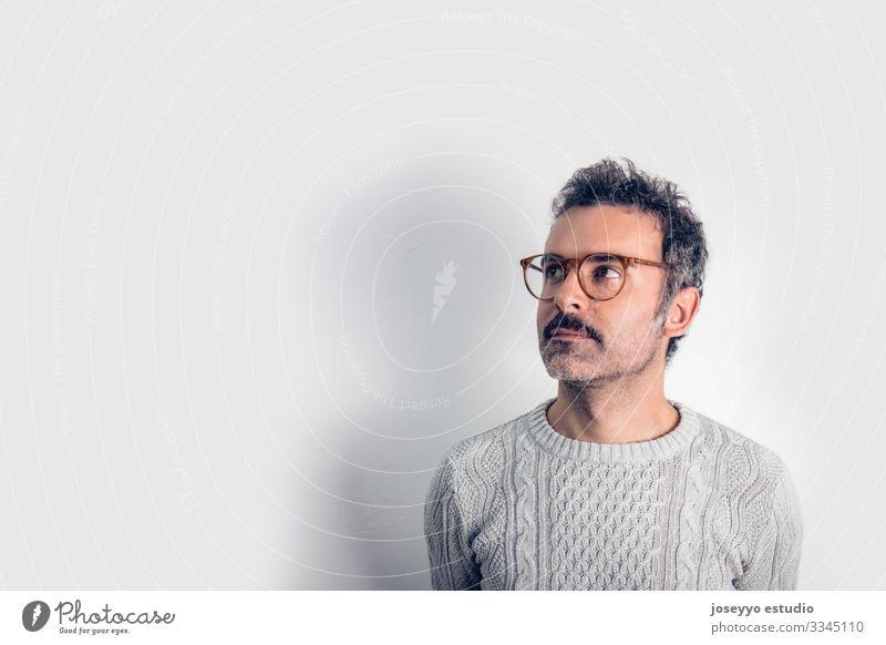 Porträt eines gut aussehenden und braun denkenden Mannes mit Schnurrbart, Brille und grauem Pullover. Grauer Hintergrund. Platz zum Kopieren Erwachsener Waffen