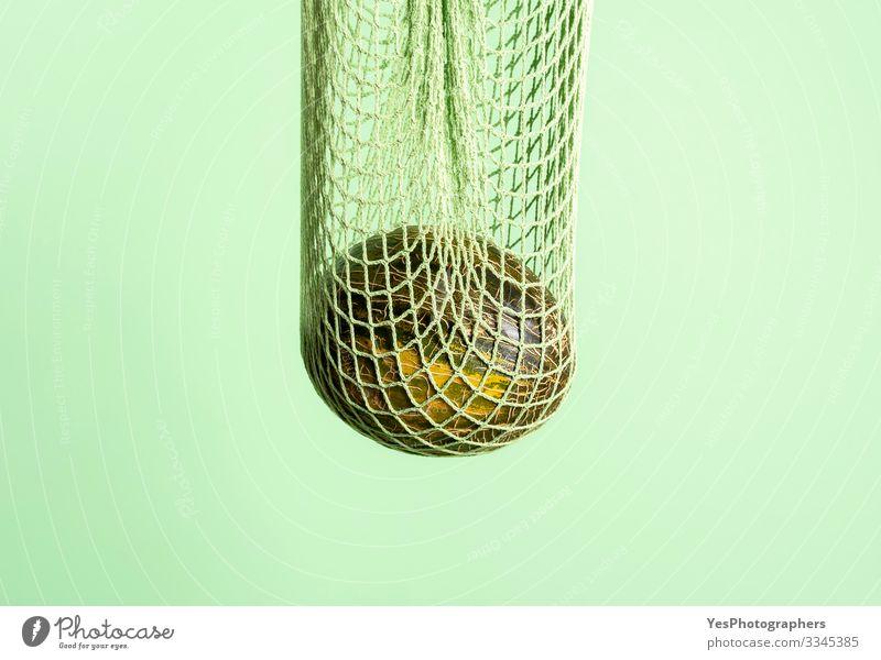 Melone in einer grünen, wiederverwendbaren Tasche. Umweltfreundliche Tasche mit Melone Frucht Gesunde Ernährung Früchte kaufen Weihnachtsmelone farbenfroh