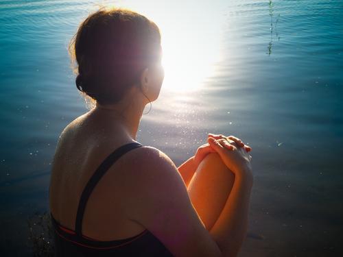 15 Minuten täglich Sonnenbad Sommer Schönes Wetter See Badeanzug brünett Zopf sitzen hell Wärme Gefühle Geborgenheit achtsam erleben Gelassenheit Pause